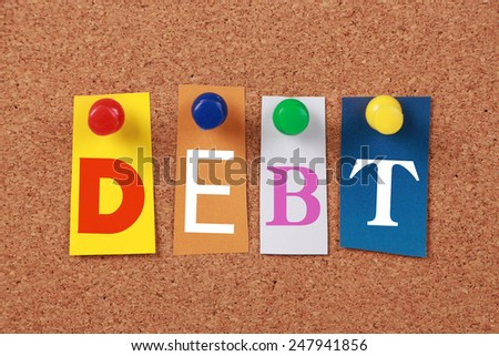 The word Debt in cut out magazine letters pinned to a cork board. - stock photo