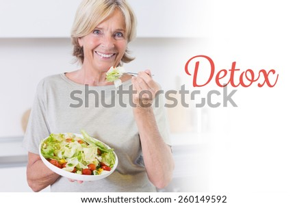 The word detox against smiling woman eating salad - stock photo