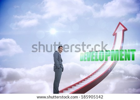 The word development and smiling businessman standing against red stairs arrow pointing up against sky