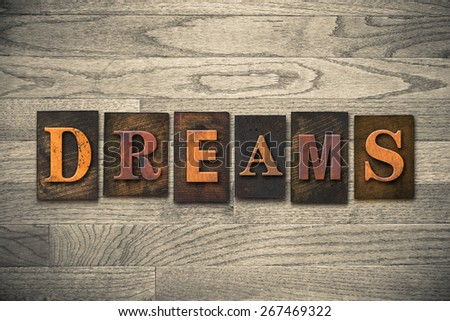"""The word """"DREAMS"""" theme written in vintage, ink stained, wooden letterpress type on a wood grained background. - stock photo"""