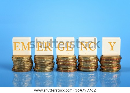 The word Emergency on stacked coins, finance conceptual - stock photo