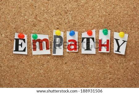 The word Empathy in cut out magazine letters pinned to a cork notice board. Empathy is the experience of understanding another person's condition from their perspective