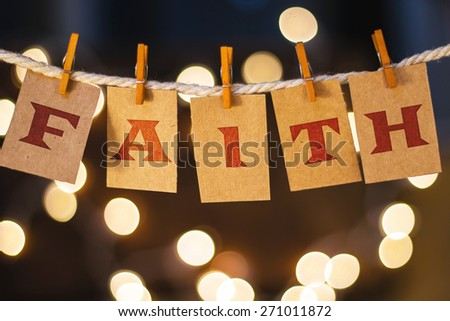 The word FAITH printed on clothespin clipped cards in front of defocused glowing lights. - stock photo