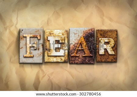 """The word """"FEAR"""" written in rusty metal letterpress type on a crumbled aged paper background. - stock photo"""