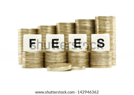 The word FEES on stacks of gold coins on a white background  - stock photo