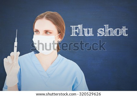 The word flu shot and pretty brunette female doctor holding a syringe and looking at it against chalkboard - stock photo