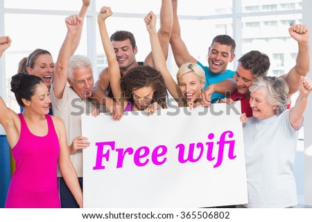 The word free wifi and excited people holding blank billboard at gym against grey wall - stock photo