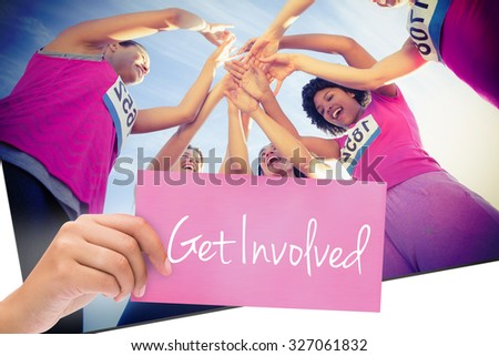 The word get involved and hand holding card against five cheering runners supporting breast cancer marathon - stock photo