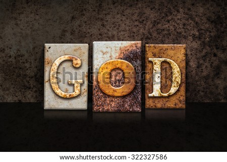 "The word ""GOD"" written in rusty metal letterpress type on a dark textured grunge background."