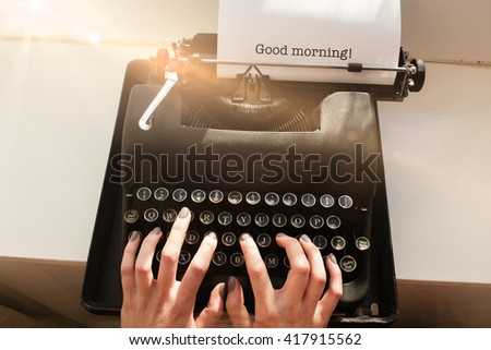 The word good morning! against womans hand typing on typewriter - stock photo