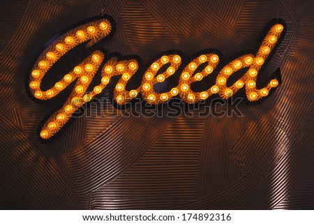 "The word ""greed"" spelled with light bulbs. - stock photo"