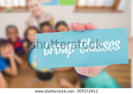 The word group classes and hand showing card against cute pupils and teacher in classroom with globe - stock photo