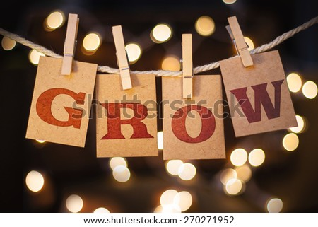 The word GROW printed on clothespin clipped cards in front of defocused glowing lights. - stock photo