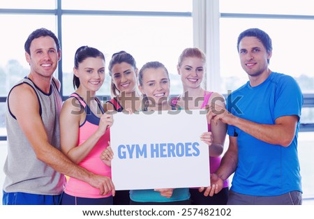 The word gym heroes against portrait of a group of fitness class holding blank paper - stock photo