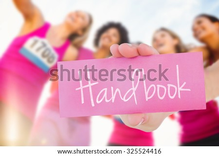 The word handbook and young woman holding blank card against runners supporting breast cancer marathon and taking selfies - stock photo