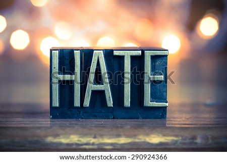 The word HATE written in vintage metal letterpress type on a soft backlit background. - stock photo