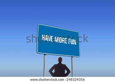 The word have more fun and businesswoman with hands on hips against bright blue sky