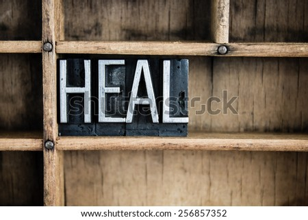 """The word """"HEAL"""" written in vintage metal letterpress type in a wooden drawer with dividers. - stock photo"""