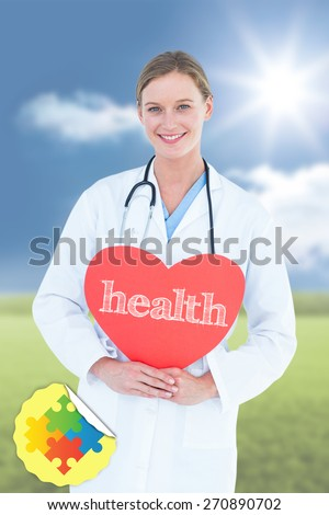 The word health and doctor holding red heart card against sunny green landscape - stock photo
