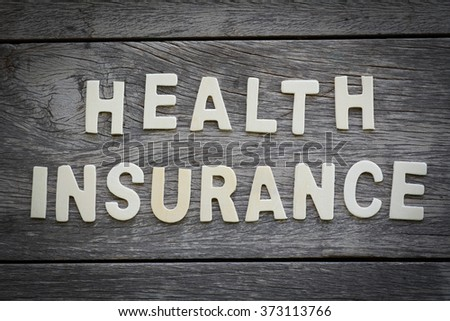 The word health insurance on the wooden floor