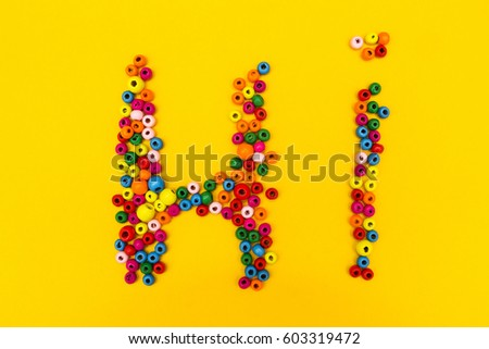 "The word ""Hi"" from multi-colored round toys on a yellow background."