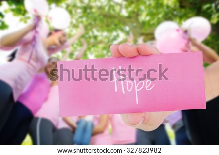 The word hope and young woman holding blank card against smiling women in pink for breast cancer awareness - stock photo