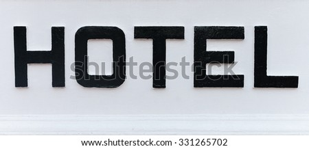 The word HOTEL in bold, black, hand painted, capital letters on a white background, part of a hotel's name sign. - stock photo