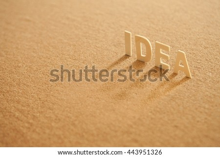 "The word "" idea "" wooden letters wooden on cork board background."