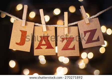 The word JAZZ printed on clothespin clipped cards in front of defocused glowing lights. - stock photo