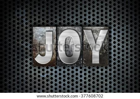 "The word ""Joy"" written in vintage metal letterpress type on a black industrial grid background. - stock photo"