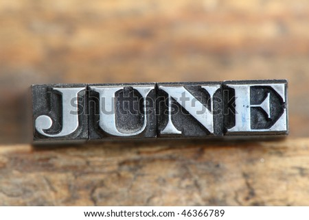 the word june in letterpress type on a wooden background. - stock photo
