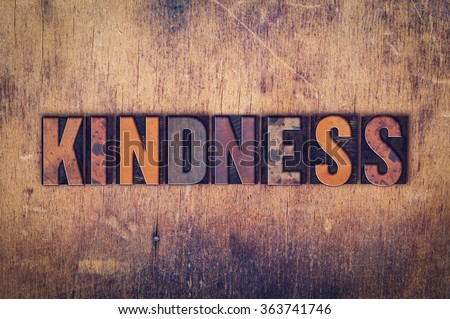 """The word """"Kindness"""" written in dirty vintage letterpress type on a aged wooden background. - stock photo"""