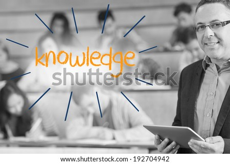 The word knowledge against lecturer standing in front of his class in lecture hall - stock photo