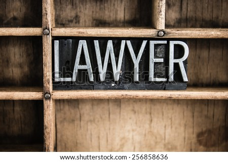 """The word """"LAWYER"""" written in vintage metal letterpress type in a wooden drawer with dividers. - stock photo"""