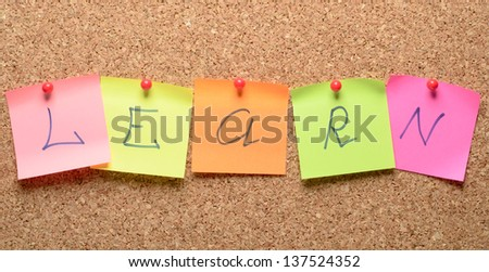 The word learn with stickers note pinned on a cork bulletin board - stock photo