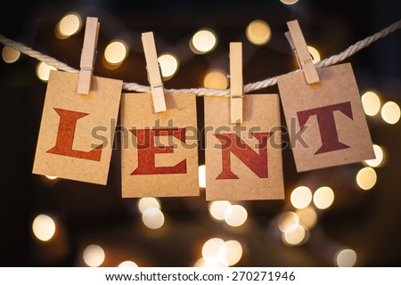 The word LENT printed on clothespin clipped cards in front of defocused glowing lights. - stock photo