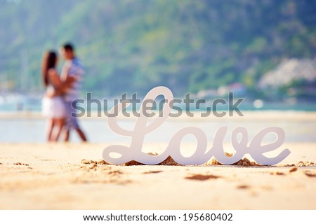 The word love and the couple in the background out of focus - stock photo