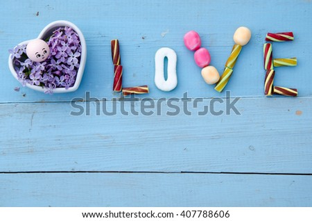The word Love in capital letters spelled out on a white background using colorful sugar-coated smarties - stock photo