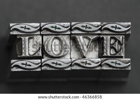 the word love in letterpress type on black background. - stock photo