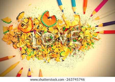 The word LOVE on the background from colored pencil shavings. instagram image retro style - stock photo