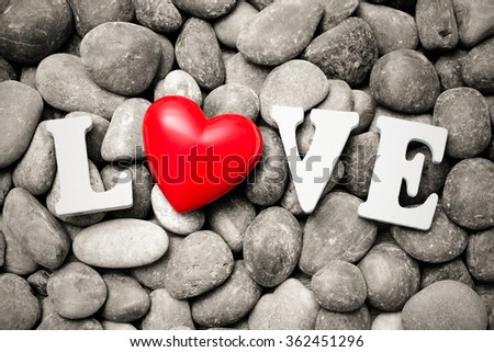 The word Love with red heart on pebble stones. Valentineâ??s Day background - stock photo