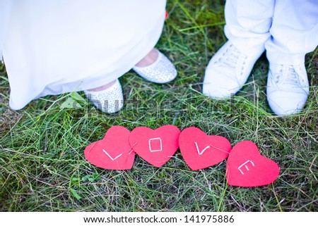 The word love written on the hearts lying on the grass on a background of the feet of the bride and groom. - stock photo