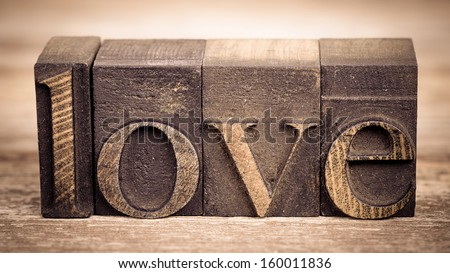 The word LOVE written with vintage printing blocks over old wood background - stock photo