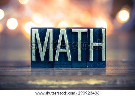 The word MATH written in vintage metal letterpress type on a soft backlit background. - stock photo