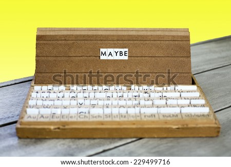 """the word """"maybe"""" on an old school letter box on a yellow background - stock photo"""