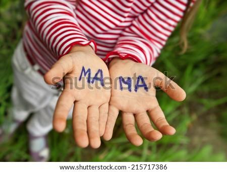 The word mom written in children's hands - stock photo