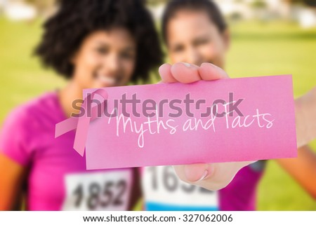 The word myths and facts and young woman holding blank card against two smiling runners supporting breast cancer marathon - stock photo