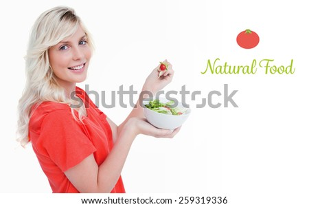 The word natural food against side view of a young woman showing a great smile while eating salad - stock photo