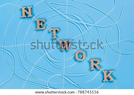 The word network with wooden letters in the form of an abstract spider web, blue background.