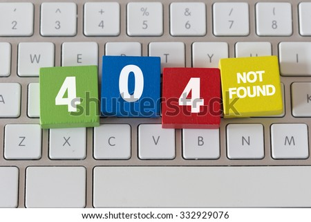 The word 404 NOT FOUND PAGE in colorful wooden cubes on the keyboard - stock photo